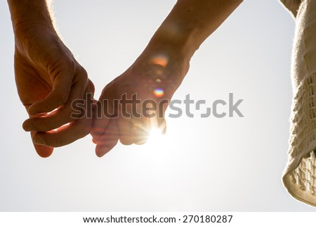 Close up Hands of Romantic Couple Holding Together with Sun Rays on a White Sky. - stock photo