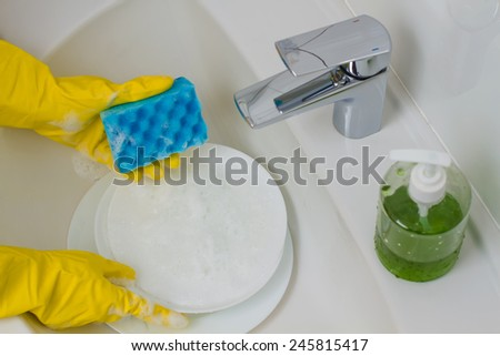 Close up hands of woman washing dishes  - stock photo