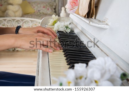 Close up hands of young woman playing piano - stock photo