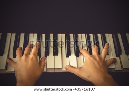 Close up  hands, playing piano. vintage tone filter effected - stock photo
