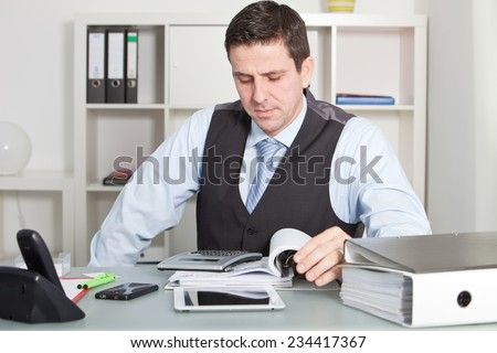 Close up Handsome Businessman Calculating Sales at his Worktable with Various Stuff like Phones, Tablet Computer and Reports - stock photo