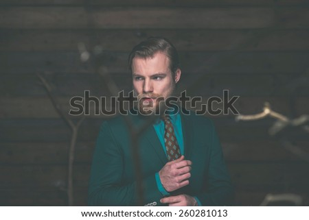 Close up Handsome Middle Age Man with Beard and Mustache Adjusting the Sleeves of his Green Formal Wear While Looking to the Left of the Frame on a Wooden Wall Background. - stock photo