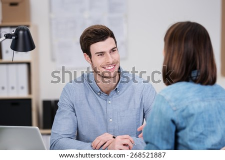 Close up Handsome Young Office Man Listening to his Female Co-Worker Talking While Sitting at his Worktable. - stock photo