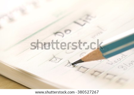 close up Handwritten to do list plan in a  small note book ,  extremely shallow DOF - stock photo