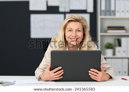 Close up Happy Adult Businesswoman Holding her Gray Laptop on the Table at her Office. Captured her While Looking at the Camera. - stock photo