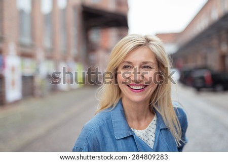 Close up Happy Adult Woman with Long Blond Hair, Laughing While Walking at the City Street - stock photo