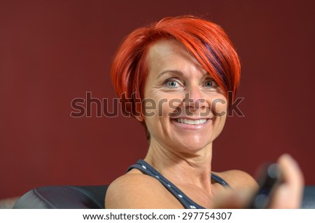 Close up Happy Face of a Middle Aged Redhead Woman Looking at the Camera with Toothy Smile Against Brown Background. - stock photo