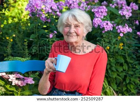 Close up Happy Grandma in Red Shirt Having a Cup of Coffee at the Garden with Flower Plants at the Background. - stock photo