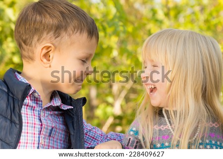 Close up Happy Little Young White Kids Playing Outdoor with Green Nature Background. - stock photo