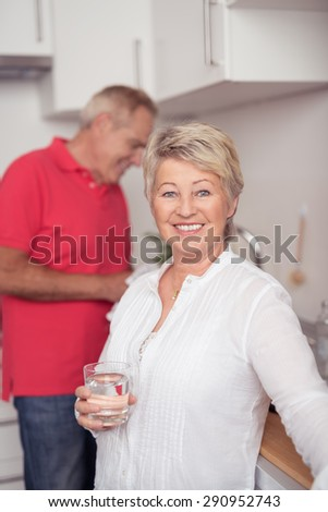Close up Happy Matured Housewife Holding a Glass of Water at the Kitchen and Smiling at the Camera - stock photo