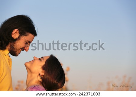 Close up Happy Sweet Couple About to Kiss on Light Blue Gray Sky Background with Copy Space for Texts on Right Side. - stock photo