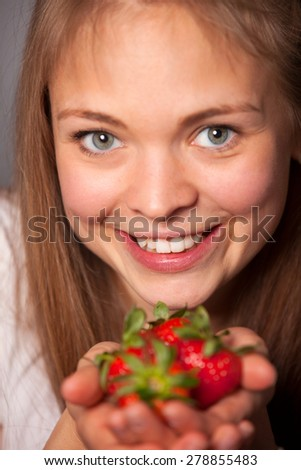 Close up Happy Young Attractive Woman Showing Fresh Strawberry Fruits on her Hand While Looking at the Camera. - stock photo