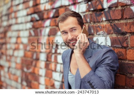 Close up Happy Young Good Looking Man Talking Someone Using Cellphone While Leaning on Old Brick Wall at the Street. - stock photo