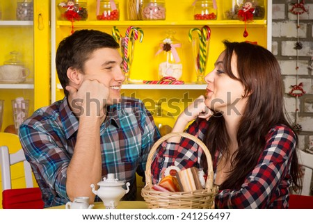 Close up Happy Young White Couple in Casual Outfits Looking Each Other with Hands on their Face While Having a Date at the Cafe. - stock photo