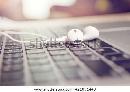 Close up Headphones on laptop at office, morning. - stock photo