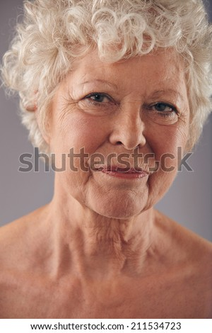 Close-up headshot of old caucasian woman face against grey background. Cropped image of senior lady. - stock photo