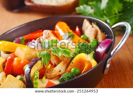 Close up Healthy Cooked Main Dish with Veggies and Spices on a Black Pan with Herbs, Placed on Wooden Table. - stock photo