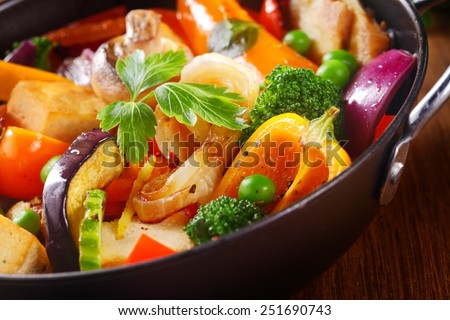 Close up Herbs on Top of Healthy Cooked Main Dish on Black Cooking Pan, Placed on Wooden Table. - stock photo