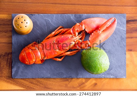 Close up High Angle Shot of Cooked Red Lobster on a Gray Cutting Board with Lime and Salt on Top of a Wooden Table. - stock photo