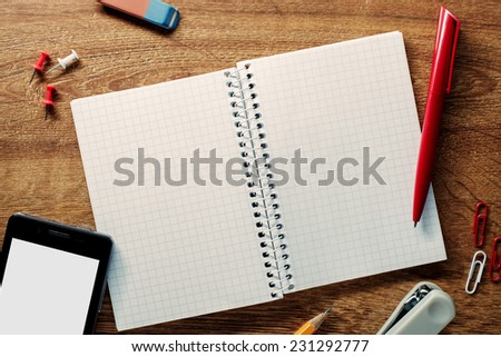 Close up High Angle View of School Supplies and Mobile Phone on Top of the Textured Table with Copy Space for Texts. - stock photo