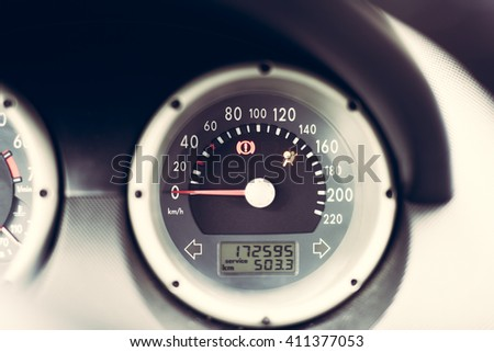 close up horizontal image of a black and white round vehicle speedometer showing that the vehicle is in starting position - stock photo
