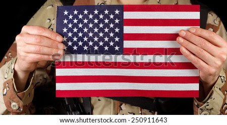 Close up horizontal image of United States of America flag with armed male soldier holding it while on black background.  - stock photo