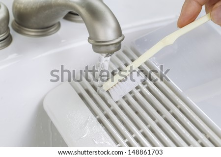 Close up horizontal photo of female hand with tooth brush cleaning bathroom fan vent cover in bathroom sink  - stock photo