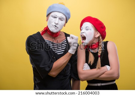 Close-up horizontal portrait of couple of two funny, male showing his fist to a female mime wanting to bite it, isolated on yellow background with copy place - stock photo