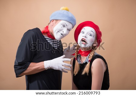 Close-up horizontal portrait of couple of two funny mimes, male mime wanting to touch and to hug a little scared female mime isolated on beige background with copy place - stock photo