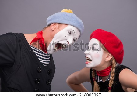 Close-up horizontal portrait of couple of two mimes standing face to face and screaming on each other isolated on grey background with copy place - stock photo