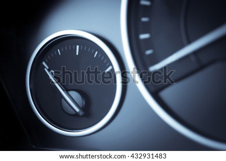 Close-up horizontal shot of a fuel gauge in a car. - stock photo