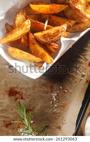 Close up Hot Spicy Potato Wedges on White Plate on Top of Oiled Paper with Powder Residue and Herbs - stock photo