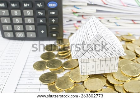 Close up house on heap of gold coins with calculator and pile of paperwork as background. - stock photo