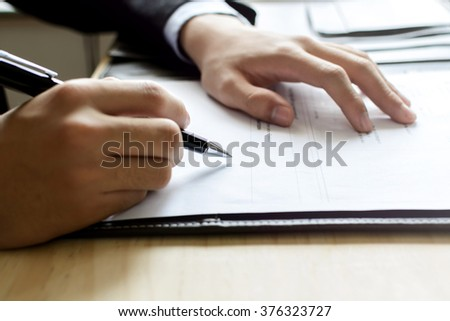 Close up Human Hand Signing on Formal Paper at the workplace - stock photo