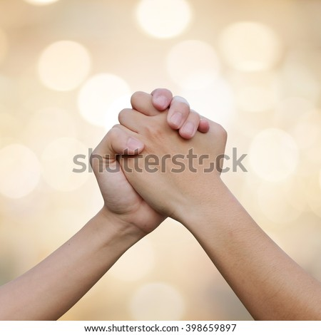close up human handshake on blur gold color background with bokeh light:man hands shake for confident,success,victory,assurance concept:trust and love of humanity conceptual idea.square frame picture - stock photo