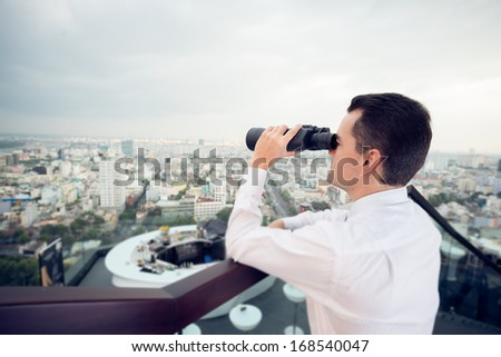 Close up image of a businessman looking at something through the binoculars on the foreground  - stock photo