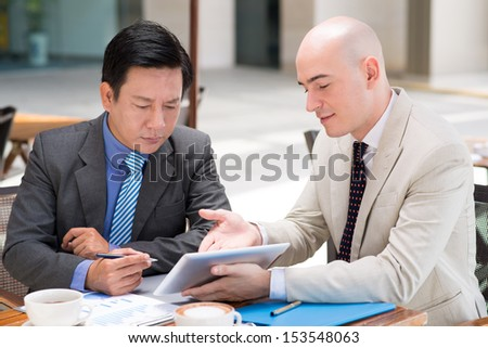 Close-up image of a businessman showing something on the tablet to his business colleague while business lunch  - stock photo