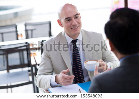 Close-up image of a Caucasian businessman with a coffecup talking with his partner during the break on the foreground - stock photo