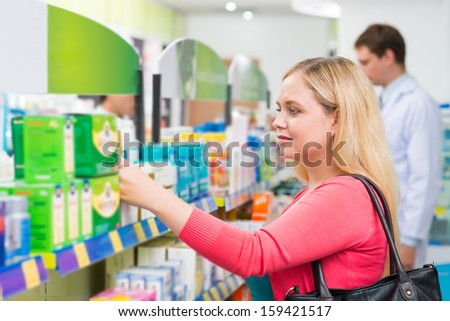 Close-up image of a female customer doing the shopping in the drugstore on the foreground - stock photo