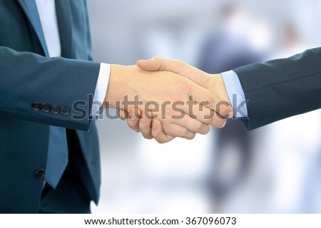 Close-up image of a firm handshake between two colleagues in office - stock photo