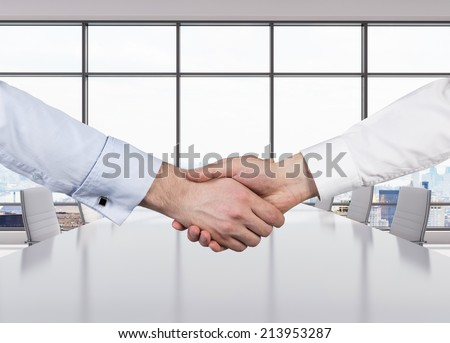 Close-up image of a firm handshake standing for a trusted partnership, modern office space. - stock photo