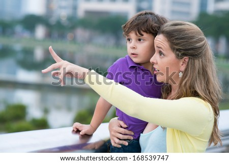 Close up image of a mother holding her son on hands and pointing at something in the street  - stock photo