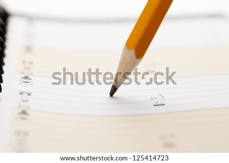 Close-up image of a pencil writing in the organizer notebook - stock photo
