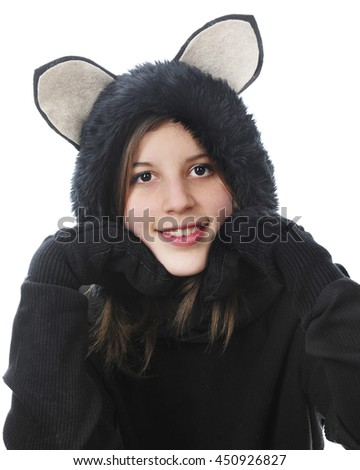 """Close-up image of a pretty young teen smiling at the viewer while dressed in a her black cat outfit and her """"paws"""" supporting her head. On a white background. - stock photo"""