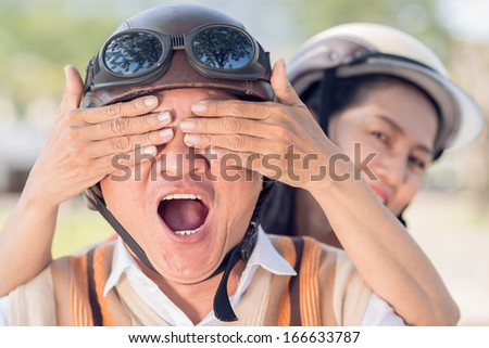 Close-up image of a senior woman covering his husband's eyes with hands, he is amazed  - stock photo