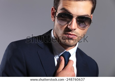 Close up image of a young elegant business man wearing sunglasses, fixing his tie. - stock photo