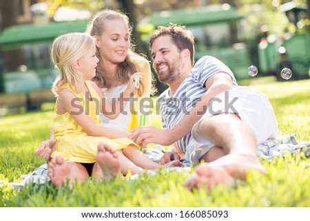 Close-up image of a young family resting in the park while a daughter blowing soap suds on the foreground  - stock photo