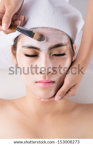 Close-up image of a young woman with facial mask at a beauty salon viewed overhead - stock photo