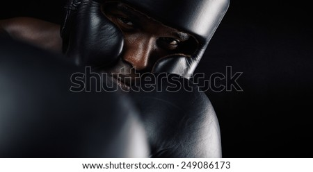Close-up image of african male boxer wearing protective head guard and gloves against black background. Young man exercising boxing. - stock photo