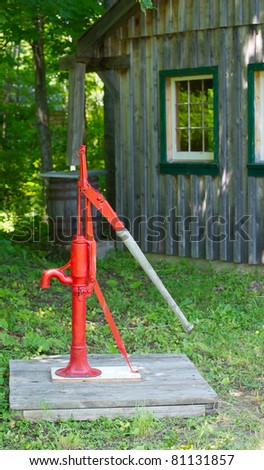 Close up image of an old red manual water pump beside a log cabin. - stock photo